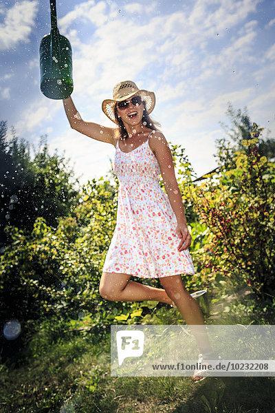 Junge Frau arbeitet im Garten  Gießkanne