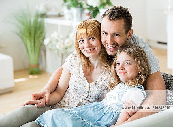 Glückliche Familie sitzend auf der Couch