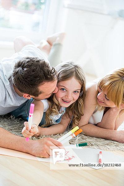Kleines Mädchen mit Eltern auf dem Boden liegend  Zeichnung mit Filzstiften