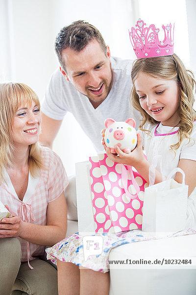 Mädchen in rosa Krone mit Geschenktüten  Eltern schauen zu