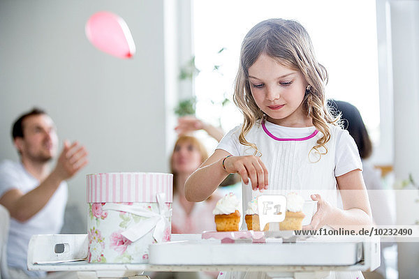 Girl Garnierung Tasse Kuchen  Familie feiert im Hintergrund
