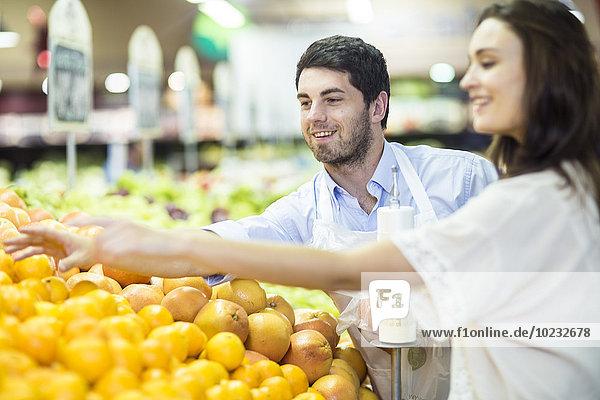 Verkäuferin hilft dem Kunden bei der Auswahl der Orangen