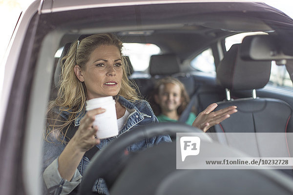 Ernsthafte Frau und Mädchen im Auto