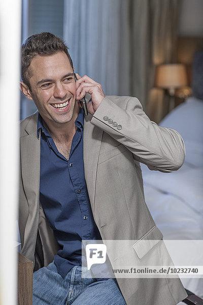 Porträt eines lächelnden Geschäftsmannes beim Telefonieren im Hotelzimmer