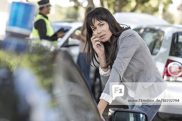 Frau am Handy am Unfallort