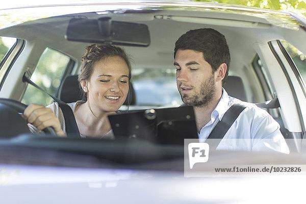 Teenagermädchen im Auto mit Fahrlehrer