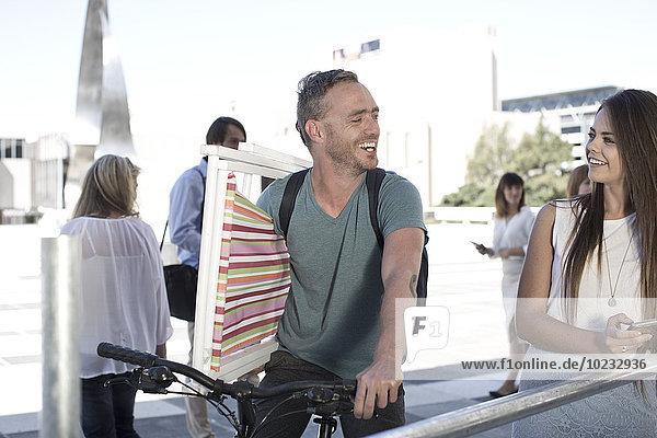 Mann auf dem Fahrrad mit Liegestuhl und Gespräch mit Frau