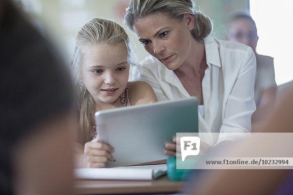 Lehrerin und Schülerin mit digitalem Tablett im Klassenzimmer