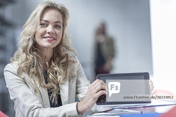 Porträt der lächelnden jungen Geschäftsfrau mit Mini-Tablette