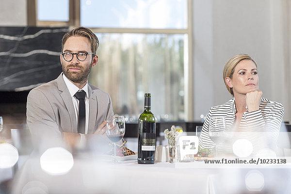 Mittleres erwachsenes Paar im Restaurant mit Kommunikationsproblemen