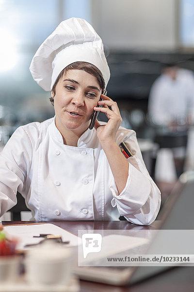 Restaurantchef am Tisch sitzend mit dem Handy