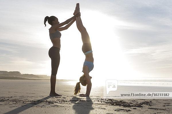 Südafrika  Kapstadt  junge Frau hilft ihrer Freundin beim Handstand am Strand