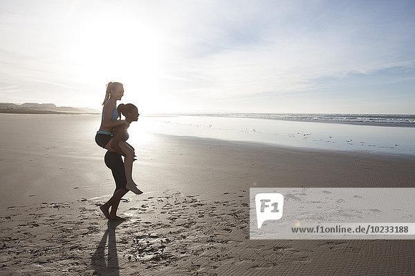 Südafrika  Kapstadt  junge Frau gibt ihrem Freund ein Huckepack am Strand