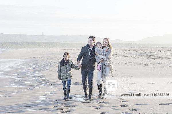 Südafrika  Kapstadt  junges Paar mit zwei Kindern  die am Strand spazieren gehen