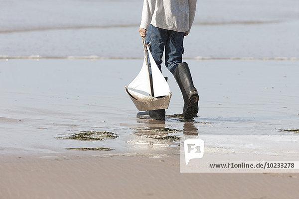 Junge spielt mit Spielzeug-Segelboot am Strand