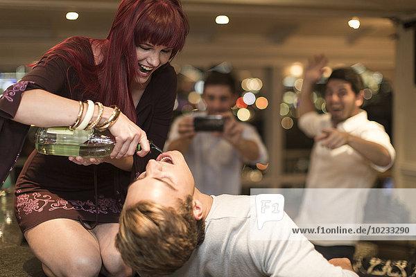 Junge Frau  die einen Mann mit Alkohol benebelt.
