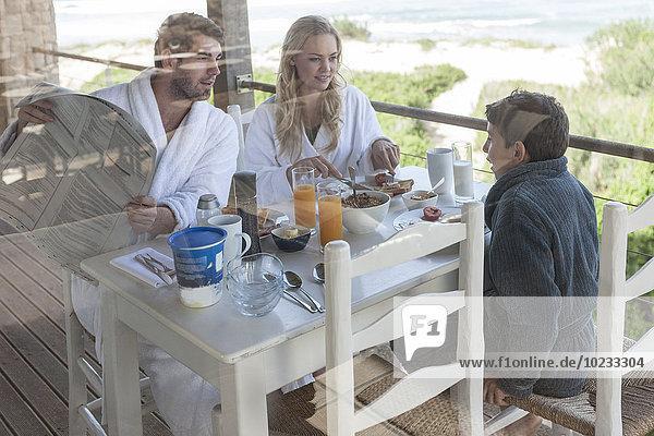 Familie auf der Terrasse des Strandhauses beim Frühstücken