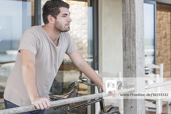 Junger Mann  der auf einer Terrasse steht und denkt.