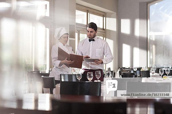 Chefkoch und Kellner im Restaurant diskutieren über das Menü