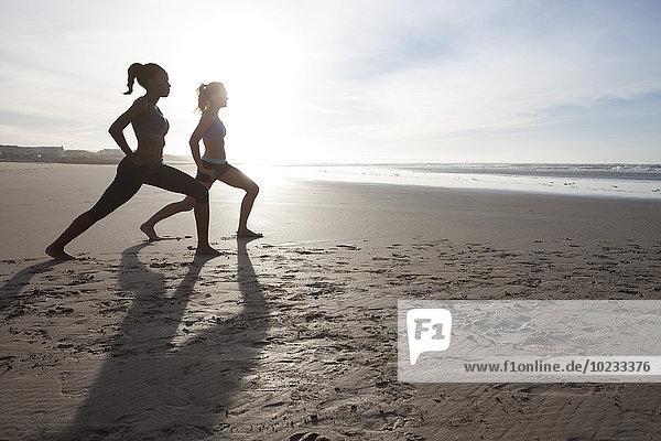 Südafrika  Kapstadt  zwei Frauen beim Stretching am Strand