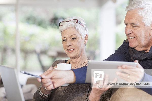 Seniorenpaar mit digitalem Tablett und Laptop