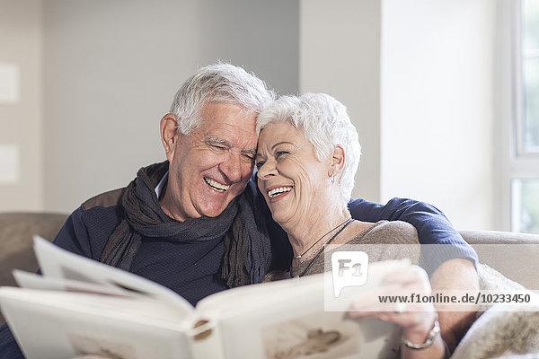 Seniorenpaar sitzend auf einer Couch mit Fotoalbum