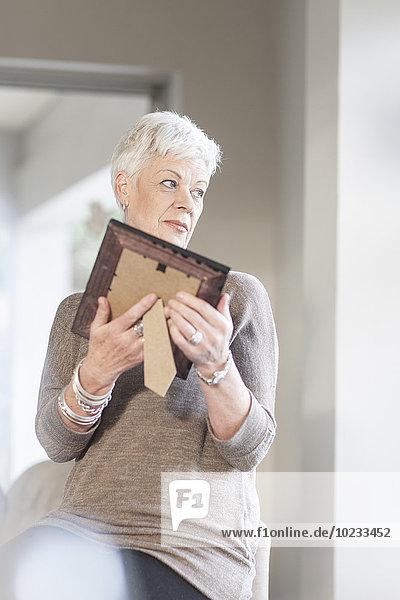 Seniorenfrau mit Bilderrahmen auf Distanz betrachtet