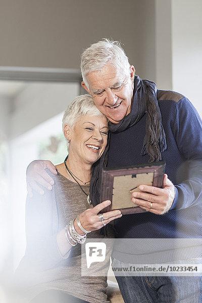 Seniorenpaar beim gemeinsamen Betrachten des Bilderrahmens