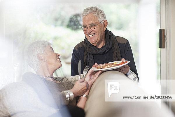 Seniorenpaar mit Teller zu Hause