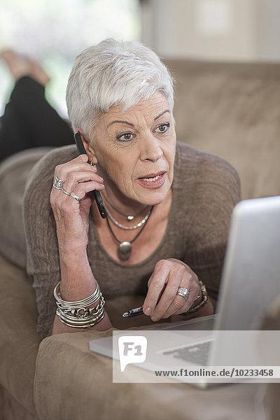Seniorin mit Laptop auf der Couch liegend und telefonierend