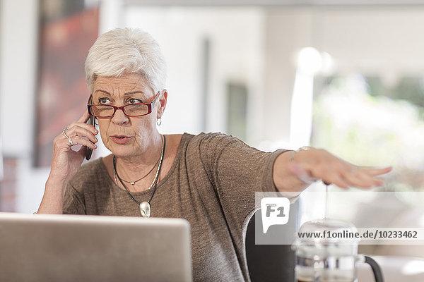 Seniorin mit Laptop am Telefon