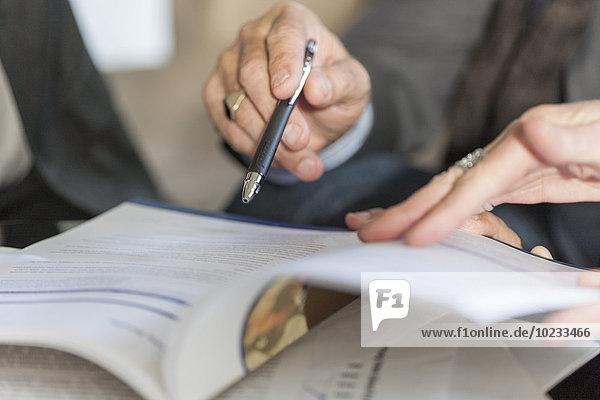 Hände halten Booklet und Kugelschreiber,  Nahaufnahme