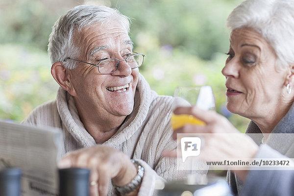 Seniorenpaar beim gemeinsamen Frühstück auf der Terrasse