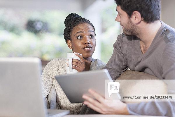 Junges Paar mit Laptop und digitalem Tablett zu Hause