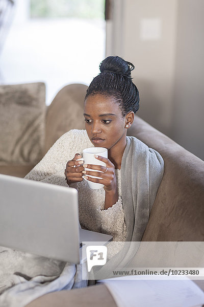 Young woman with laptop drinking coffee at home