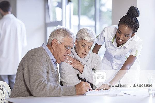 Krankenschwester  die sich um ältere Paare kümmert