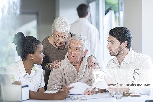 Seniorenpaar in der Klinik im Gespräch mit Arzt und Krankenschwester