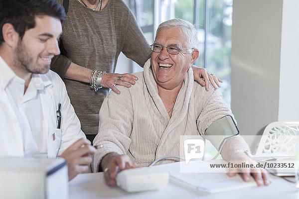 Glücklicher älterer Mann in der Klinik mit Frau und Arzt