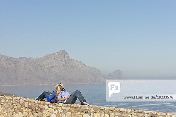Südafrika  zwei Frauen sitzen Rücken an Rücken an Rücken an einer Wand an der Küste