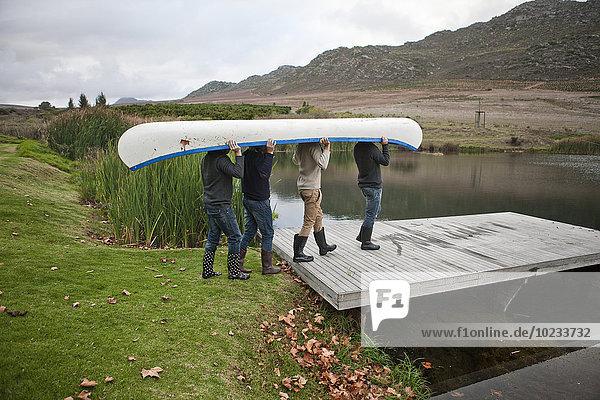 Vier Freunde  die ein Kanu zu einem See tragen.