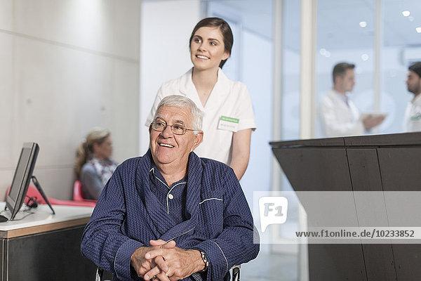 Krankenschwester mit Patient im Rollstuhl an der Klinikrezeption