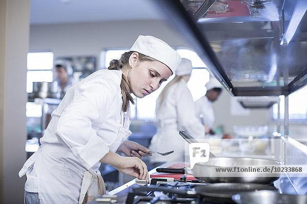 Teenagermädchen beim Kochen in der Großküche
