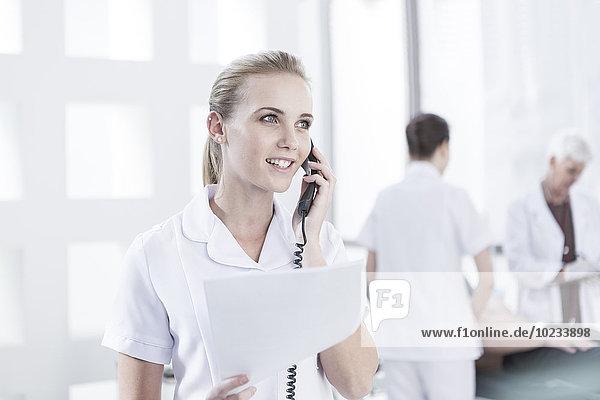 Krankenschwester im Krankenhaus mit Unterlagen am Telefon