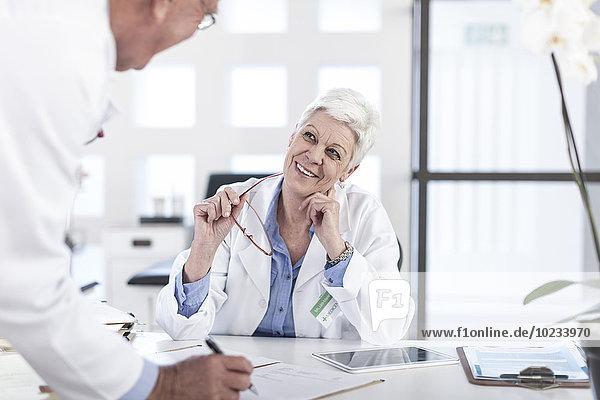 Zwei Ärzte im Gespräch am Schreibtisch
