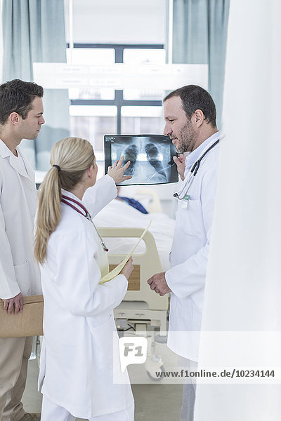Three doctors with x-ray image in a hospital room