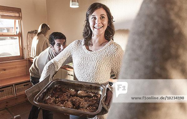Lächelnde Frau in der Küche serviert Mahlzeit