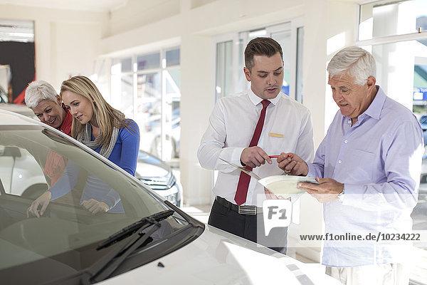 Senior unterschreibt Kaufvertrag beim Autohändler