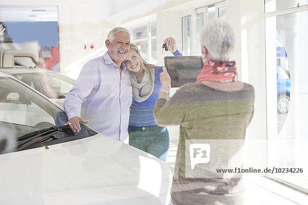 Mutter fotografiert glücklichen Vater und Tochter mit Autoschlüssel
