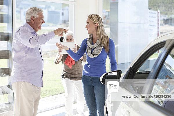 Ein älterer Mann kauft ein neues Auto für seine Tochter.