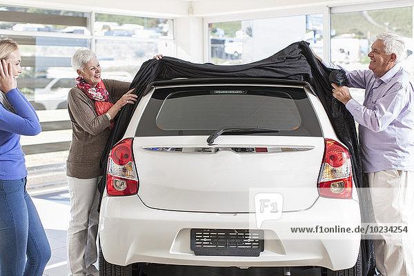 Vater und Mutter enthüllen neues Auto als Geschenk für die Tochter